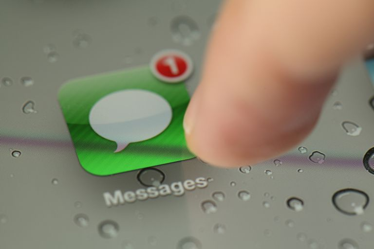 A finger pressing the Message button on an iPhone