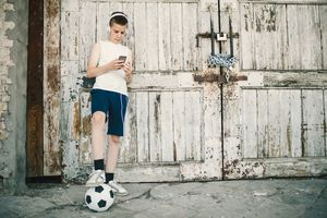 Boy with soccer ball in front of fence