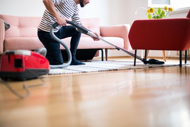 A man vacuuming his rug.