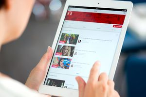 A woman using the official YouTube app on an Apple iPad