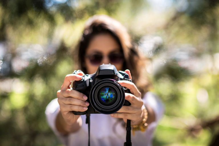 A woman holding a DSLR camera.
