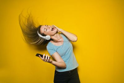 Girl wearing headphones and hold phone while singing.