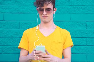 Skinny man in yellow t-shirt listening to bad music on his iPhone
