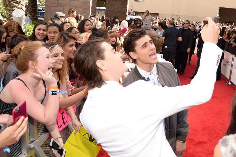 Celebrity teens taking selfies with fans on the red carpet