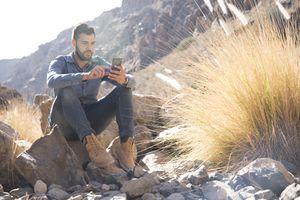 Hiker using smartphone in desert