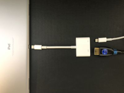 Photo of an iPad, with a Lightning-to-HDMI adapter, and an HDMI cable and Lightning power cable about to connect