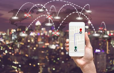Photo illustration of a phone with map directions over a map of the world with some destination crossed out.