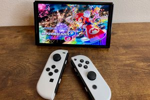 The new Switch OLED console in tabletop mode with detached white joy-con controllers and MarioKart 8 on screen.