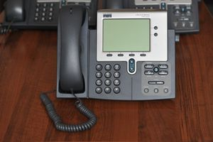 Stock photo of a Cisco Systems IP desk phone sitting in front of two other phones on a desk.