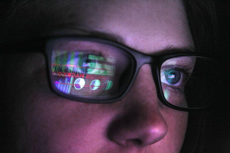 Close up of face with glasses with the reflection of computer screen in glasses