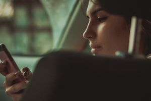 Young Woman Holding Smart Phone In Car