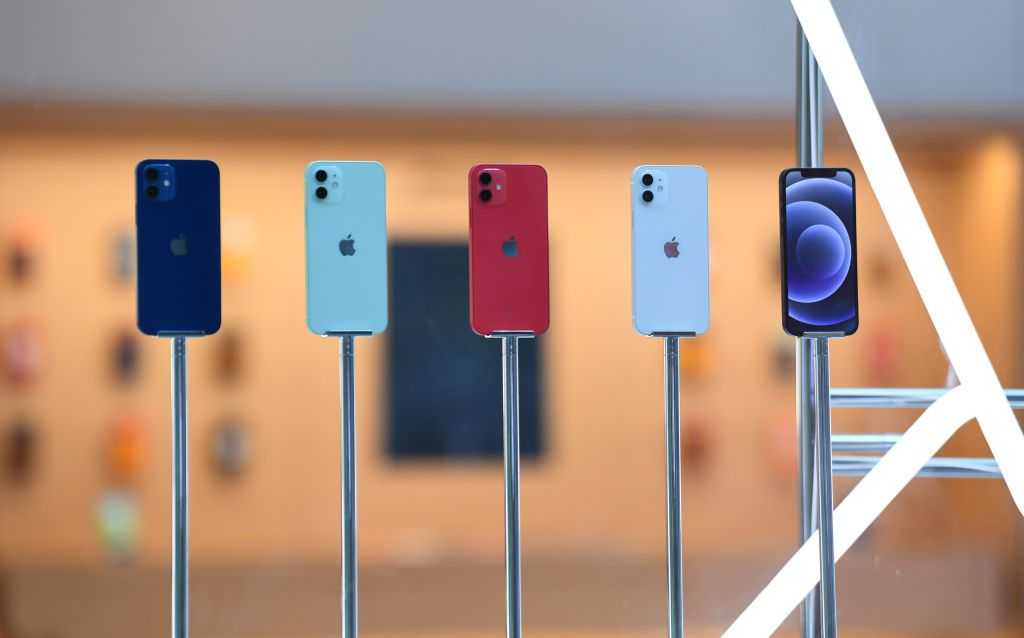 A line up of the new Apple iPhone 12 inside the window of an Apple Store