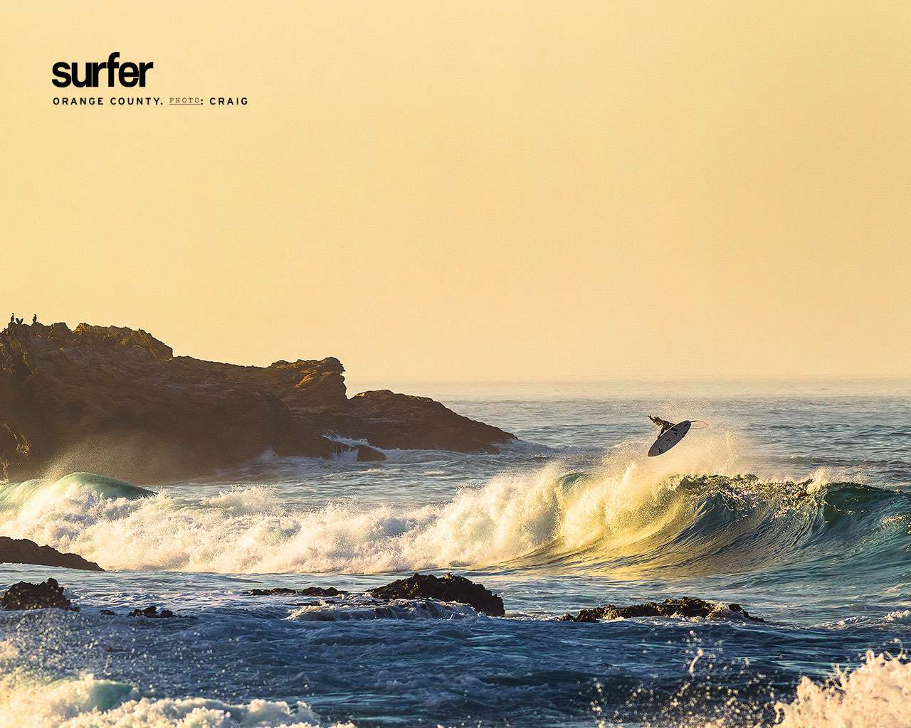 Free ocean wallpaper featuring a surfer in mid flip above a wave near rocks and cliffs