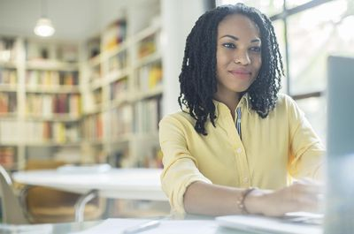 Woman working at laptop in room with bookshelves