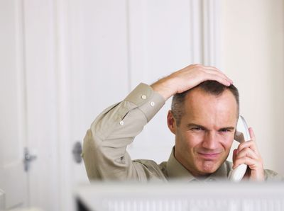 A man holding his head in his hand on an annoying phone call
