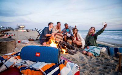 Partygoers on a beach listening to a JBL speaker