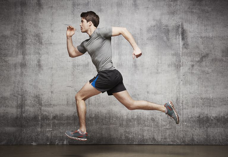 Photograph showing a muscular male runner in an urban studio