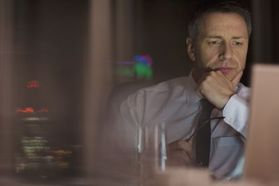 Pensive businessman working late at laptop in office
