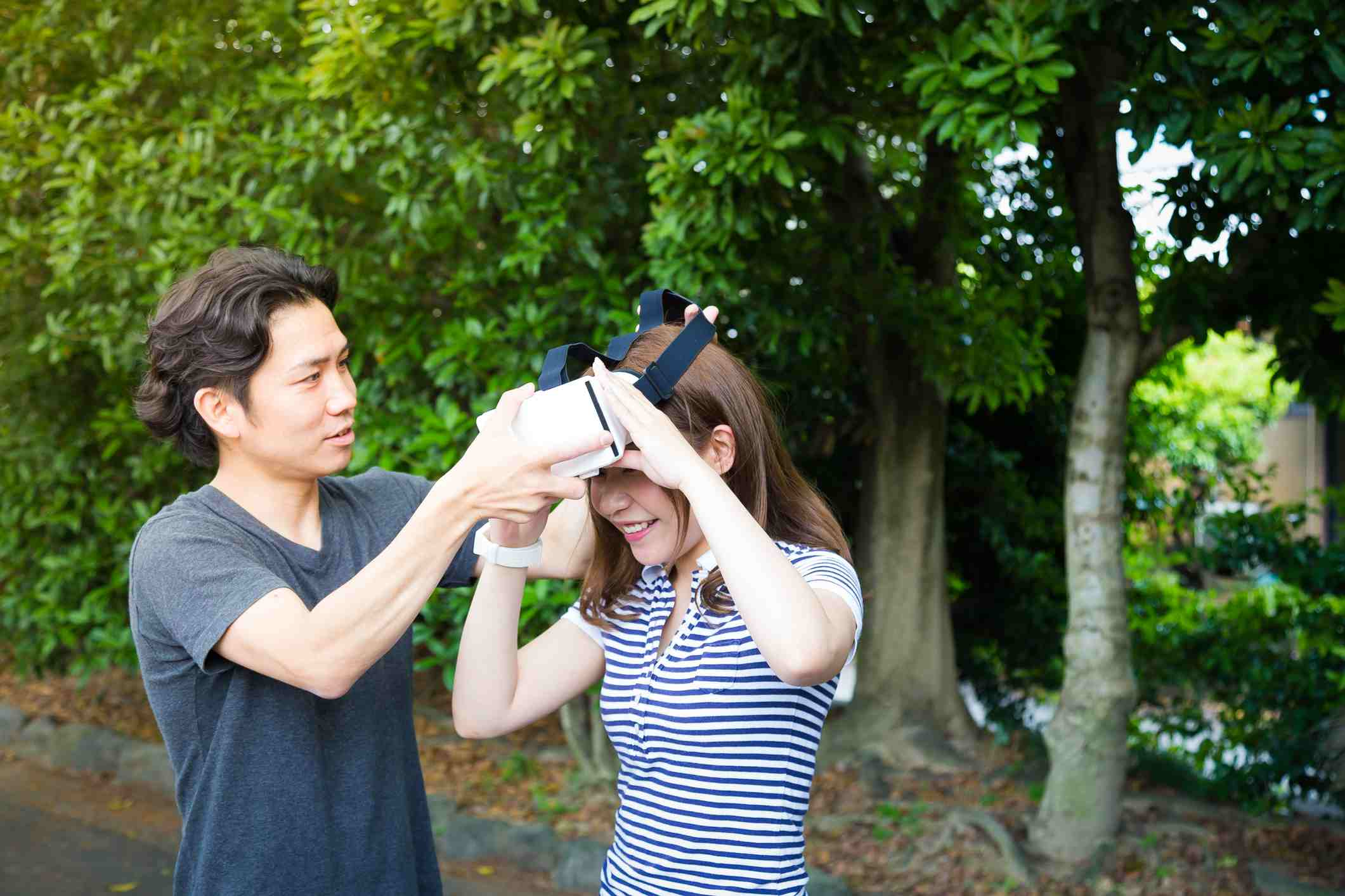Man taking VR set off of girl's head