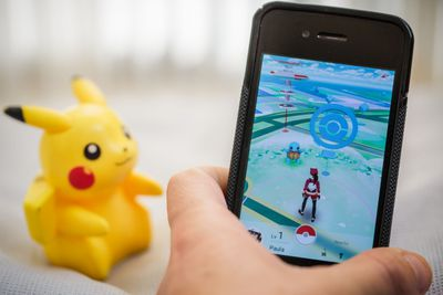 Pokemon Go on a smartphone with a Pikachu toy in the background