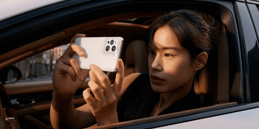 Oppo Find X3 Pro in the hands of a person in a car