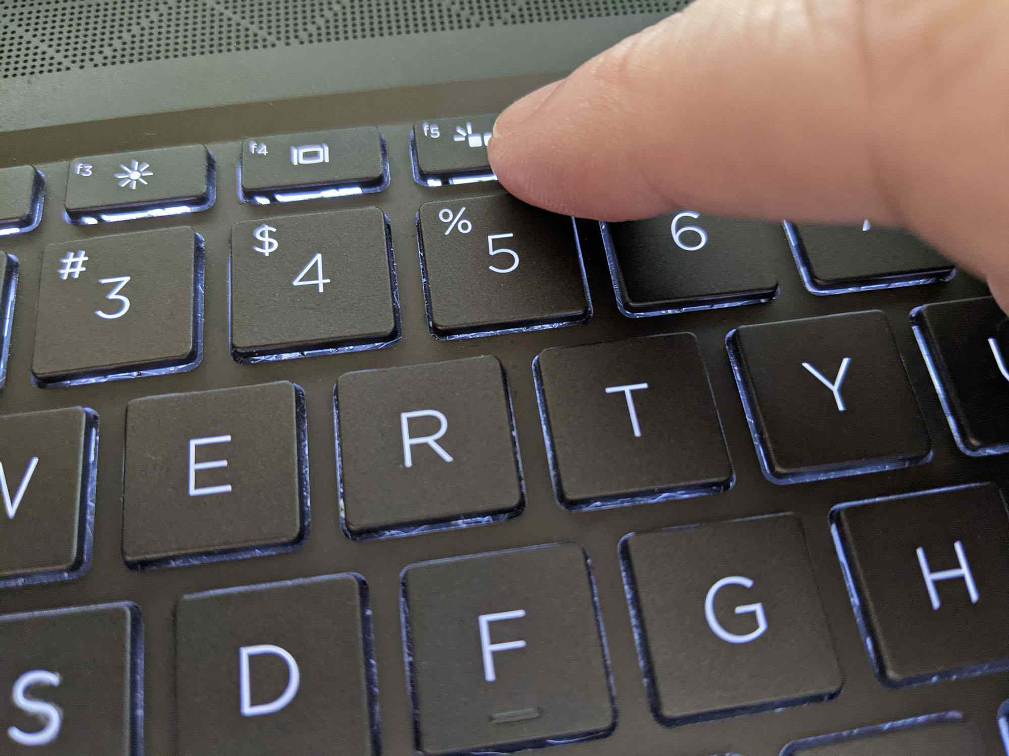 Pressing the keyboard light button on a Windows laptop.