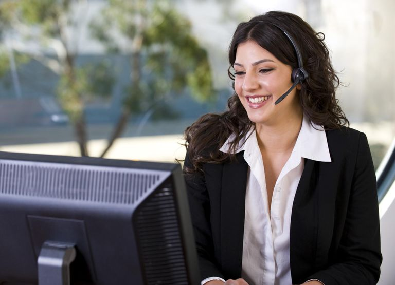 Attractive woman talking with a headset and typing