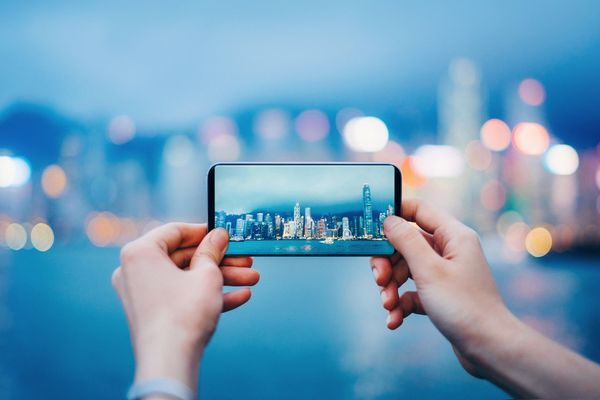 A person using a smartphone to take a picture of a city.