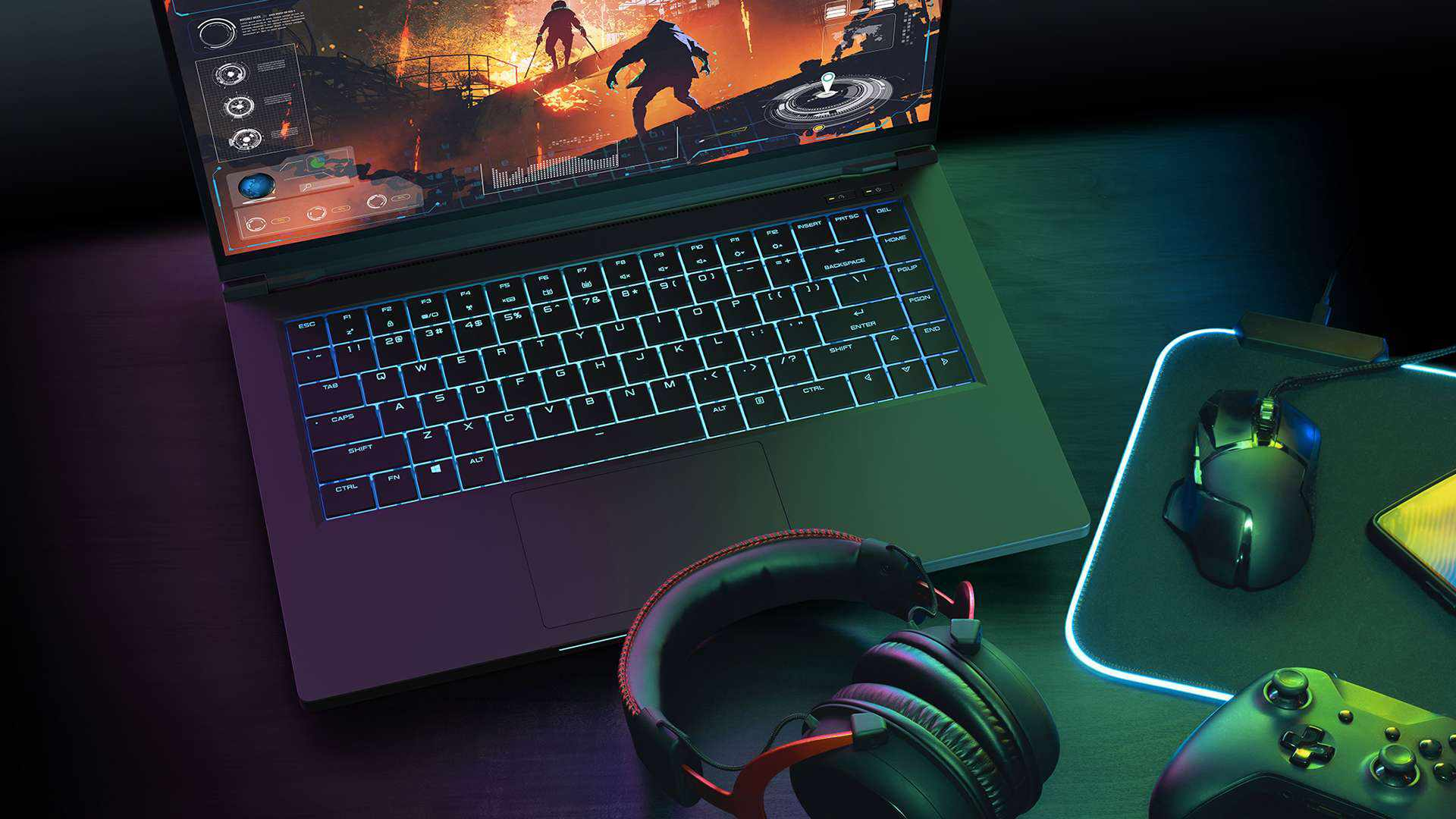 A gaming laptop on a desk with headphones, a mouse, and a game controller nearby.