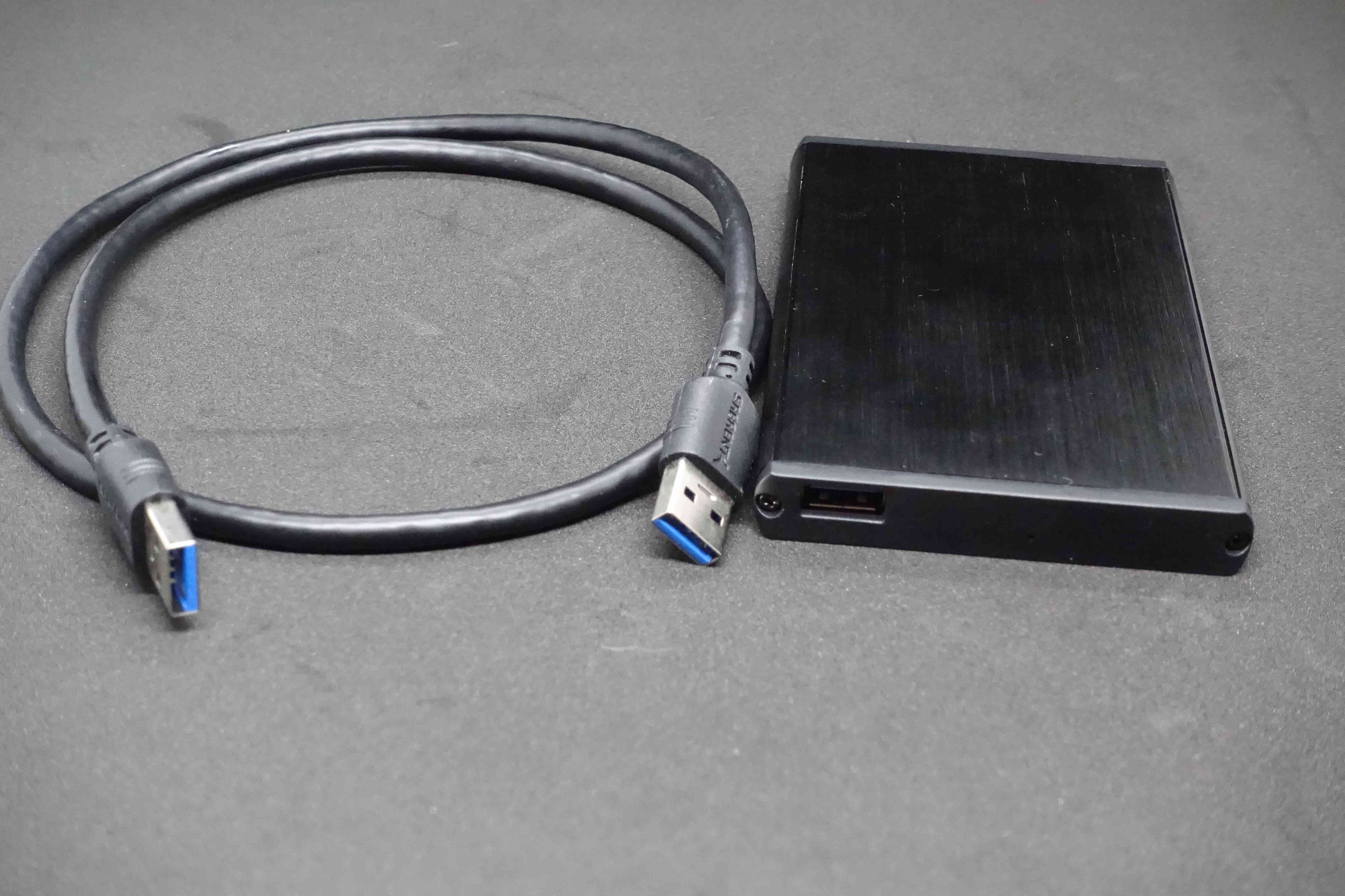 An external hard drive with a USB cable.