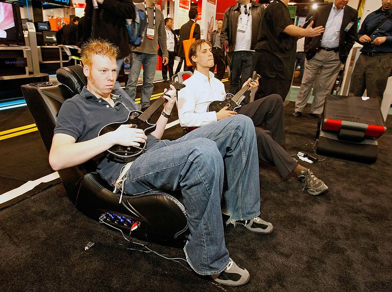 Two guys sitting in gaming chairs playing Guitar Hero