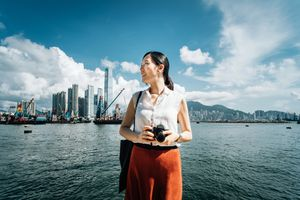 Woman with a camera standing in front of a city