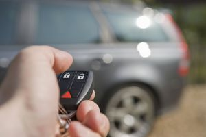Key fob pointed at a SUV in the background