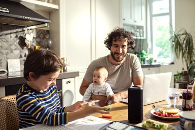 A man holding a baby while sitting at a kitchen table with another child nearby and a smart speaker on the table