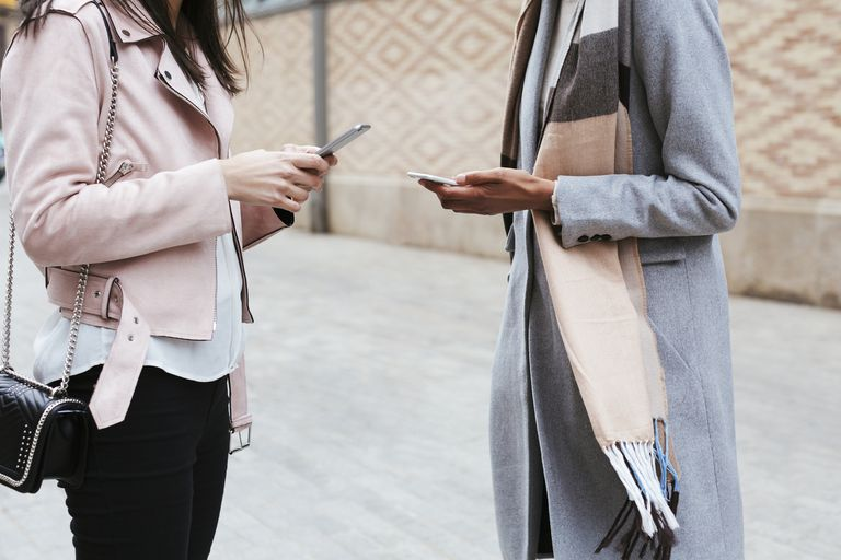 Two people using smartphones to message