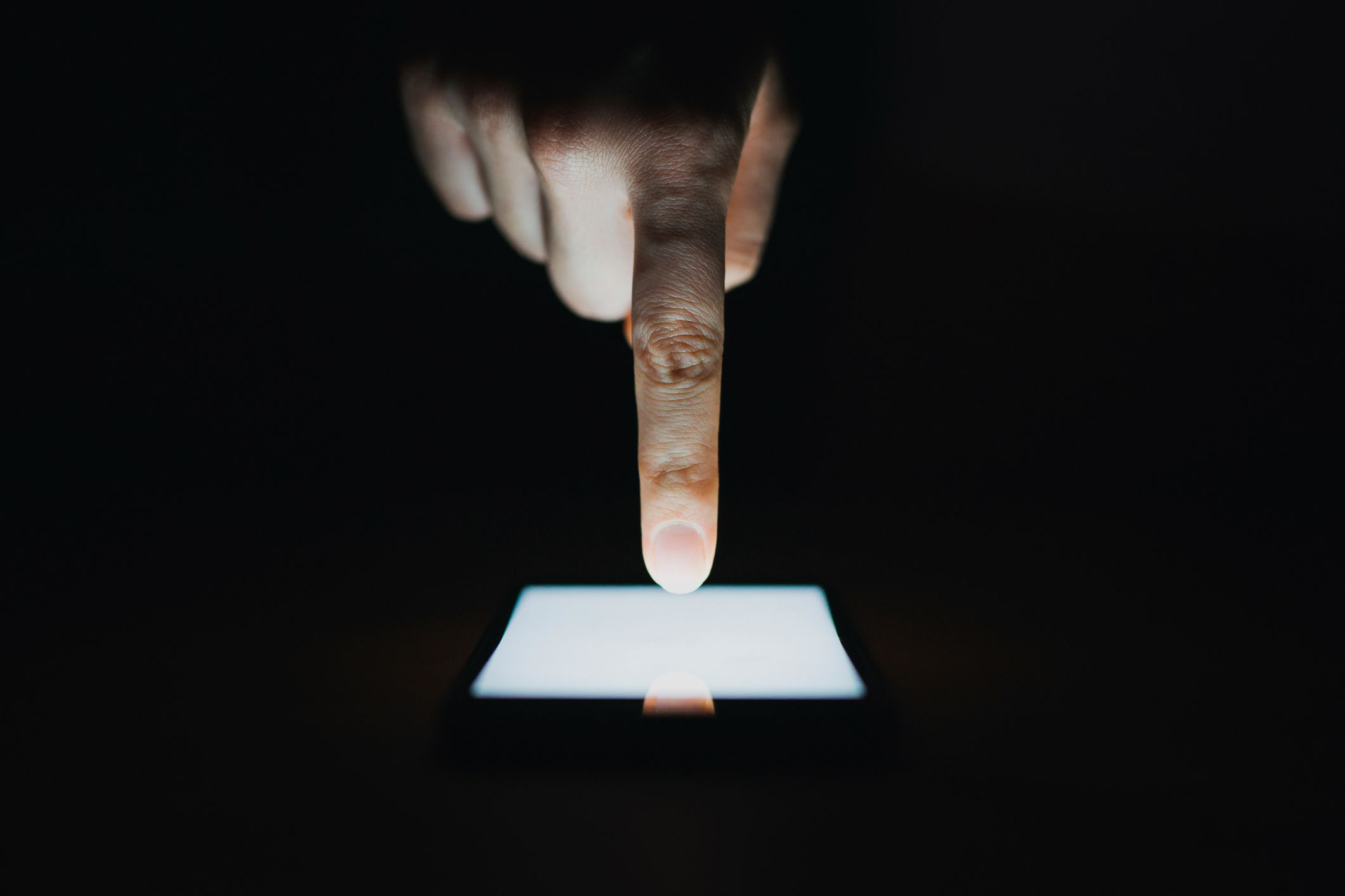 Close up of a hand using a smartphone in the dark