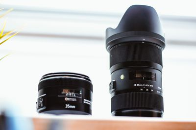 Two camera lenses on a shelf