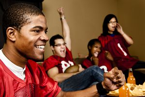Football fans at home watching, cheering. Sports game on television.