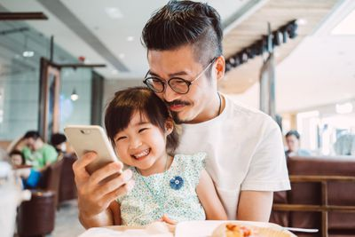 Young dad using smartphone with little daughter