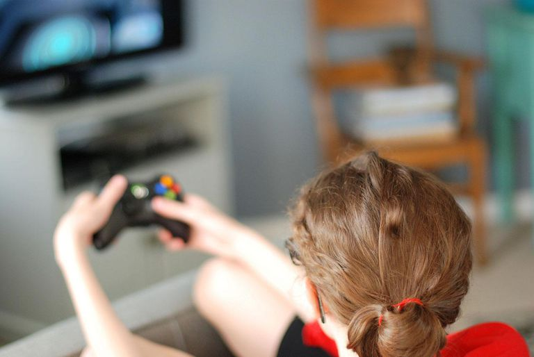 Girl with pony tail playing video game, viewed from behind.