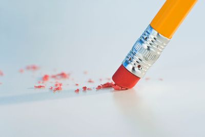The eraser end of a pencil rubbing on a white surface