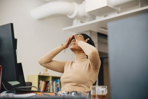 A stressed-out woman sits at her desk and rubs her eyes.