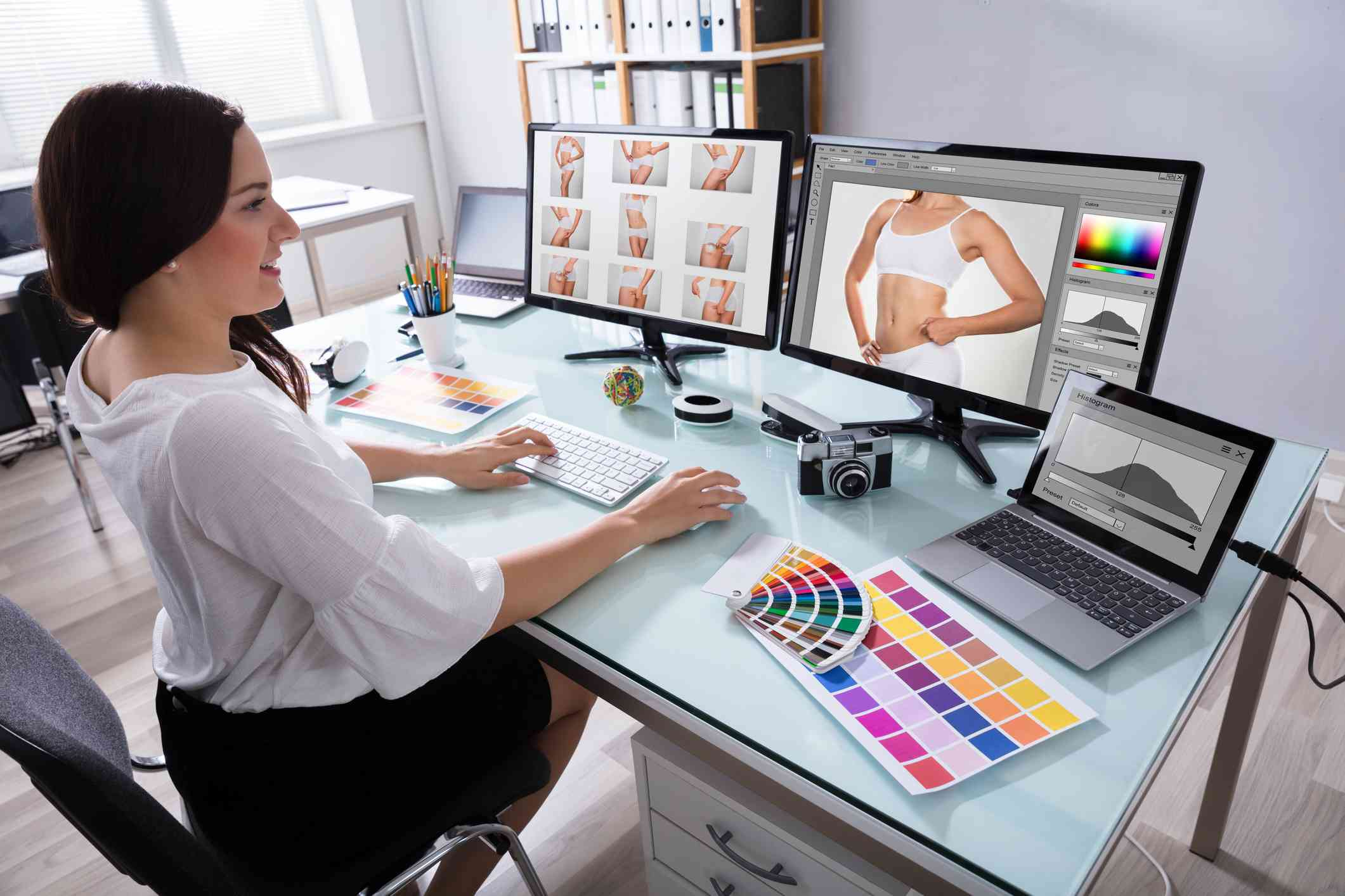 Someone retouching photos on two computer screens in a home office.