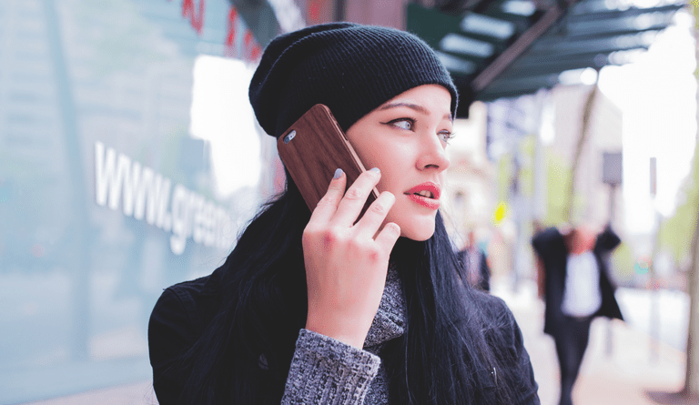 Image of a woman answering a cellphone.