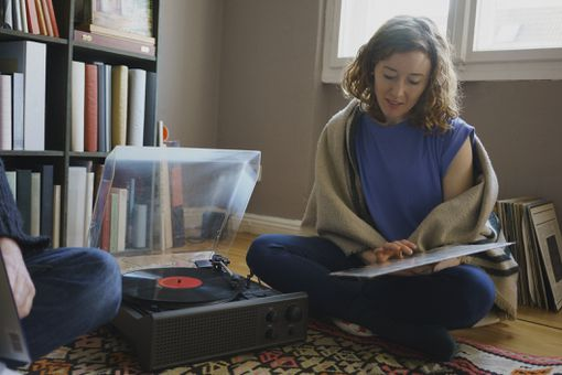 Young woman playing records on a turntable on the floor