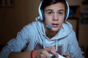 Teenage boy playing a Sony PlayStation video game wearing a white and blue headset