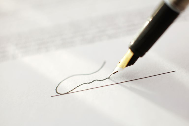 Close up of signing contract with signature.