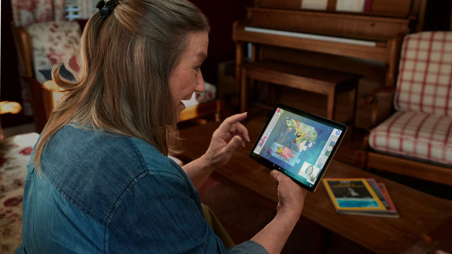 Woman using tablet to interact with Amazon Glow