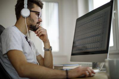 Man wearing headphones using a spreadsheet app on a computer.