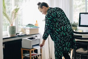 Woman using a desktop printer at home